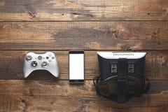 Begreppet av smart dobbel bästa sikt av gamepad, smartphone, VR-exponeringsglas på träbakgrund med kopieringsutrymme royaltyfri fotografi