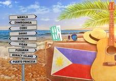 Begreppet av sommarresanden med den gamla resväskan och Filippinernastaden undertecknar Royaltyfria Foton