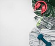 Begreppet av sportar livsstil, sportswear och tillbehör ställde upp på en vit bakgrund, med flaskan av vatten och tropiska sidor Fotografering för Bildbyråer