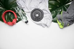 Begreppet av sportar livsstil, sportswear och tillbehör ställde upp på en vit bakgrund, med flaskan av vatten och tropiska sidor royaltyfri bild