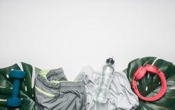 Begreppet av sportar livsstil, sportswear och tillbehör ställde upp på en vit bakgrund, med flaskan av vatten och tropiska sidor Royaltyfri Foto
