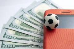 Begreppet av sportar som slå vad med en smartphone En fotbollsouvenirboll på hörnet av en mobiltelefonskärm i en röd fallaga arkivbilder