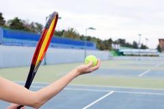 Begreppet av sporten och utomhus- aktiviteter En lek med en stor tennis - en hand med en boll och en racket arkivbilder