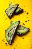 Begreppet av sund mat, en smörgås för rågbröd med avokadot och ost på en gul bakgrund, vertikalt fotografering för bildbyråer