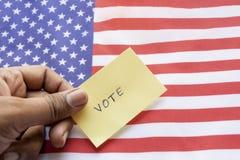 Begreppet av USA-valet, röstar klistermärkeinnehavet i hand på USA-flagga royaltyfri fotografi