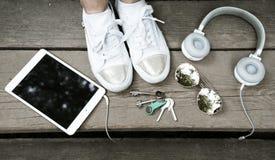 Begreppet av vit färg, hörlurar, minnestavlan, exponeringsglas, gymnastikskor och tangenter ligger på en träyttersida Kontor i pa Royaltyfri Bild