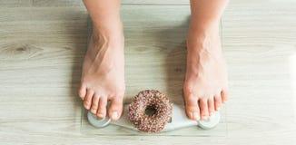 begreppet bantar Närbild av fot för kvinna` s på vägningsskala med munken Begrepp av sötsaker, sjuklig skräpmat och fetma Royaltyfri Bild
