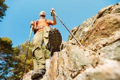 Begreppet den unga mannen med skägget reser till och med berget, det turist- ryggsäckanseendet vaggar på kullen, medan tycka om Arkivfoton