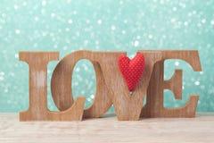 Begreppet för dagen för valentin` s med träbokstäver förälskelse och hjärta formar över bokehbakgrund Fotografering för Bildbyråer