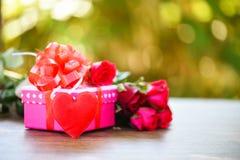 Begreppet för förälskelse för blomman för asken för valentindaggåvan/den rosa gåvaasken med röda rosor för bandpilbågen blommar royaltyfri foto