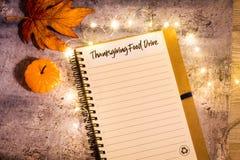 Begreppet för listan för tacksägelsematdrev på anteckningsboken som omges med ljusa sidor och dekorativa ljus, lägenhet lägger royaltyfri fotografi