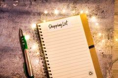 Begreppet för shoppinglistan på anteckningsboken som omges med ljusa sidor och dekorativa ljus, lägger framlänges royaltyfri fotografi
