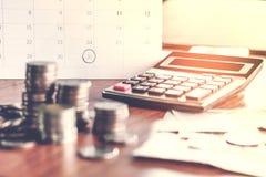 Begreppet för skuldsamlingen och skattsäsongmed stopptidkalendern påminner anmärkningen, mynt, banker, räknemaskin på tabellen Royaltyfria Bilder