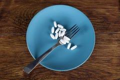 Begreppet för viktförlust av bantar preventivpillerar på plattan med gaffeln Fotografering för Bildbyråer