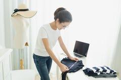 Begreppet för visningslokalen för modeformgivaren är det stilfulla, den unga asiatiska flickan freelanceren med hennes hemmastadd royaltyfri foto