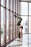 Begreppet för yoga för den unga attraktiva yogikvinnan som poserar det övande står i variation av den Pincha Mayurasana övningen, arkivfoton