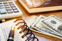 begreppet finansierar home Dollarräkningar och räknemaskin Royaltyfri Foto