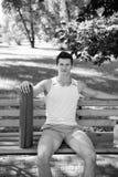 begreppet kopplar av Idrottsman nen kopplar av på bänk parkerar in Idrottsmannen kopplar av efter yogautbildning tyck om livstid  royaltyfri fotografi