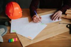 Begreppsarkitekter, iscensätter den hållande pennan som pekar utrustningarkitekter på skrivbordet med en ritning i kontoret arkivbilder