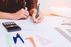 Begreppsarkitekter, iscens?tter den h?llande pennan som pekar utrustningarkitekter p? skrivbordet med en ritning i kontoret arkivbild