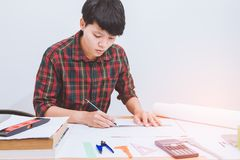 Begreppsarkitekter, teknikerinnehavpenna som pekar utrustningarkitekter på skrivbordet med en ritning royaltyfria bilder