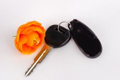 Begreppsbakgrund för auto återförsäljare och hyra Tangenter med en orange blomma Biltangent och larmsystem på vit bakgrund En gåv royaltyfri foto