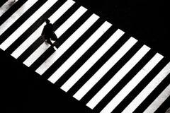 Begreppsbild av en man som går över zebramarkering arkivfoton
