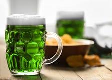 begreppsdagpatrick st Exponeringsglas av grönt öl arkivfoto