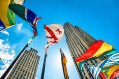 Begreppsfoto av den globala internationella företags affären Skyskrapor och internationalen sjunker mot blå himmel på den soliga  Royaltyfria Foton