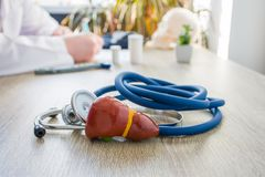 Begreppsfoto av diagnosen och behandling av lever I förgrund är modellen av levergallbladderen nära stetoskopet på tabellen i bac fotografering för bildbyråer