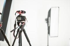 Begreppsintervju, digital kamera på en tripod med en mikrofon i studion på en vit bakgrund royaltyfri bild