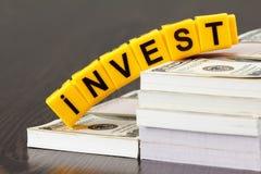 Begreppsinvesteringar, ord som genom brev göras, bunt av dollarräkningar arkivfoto