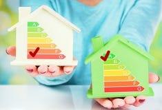 Begreppsjämförelse mellan det normala huset och det låga förbrukningshuset med energieffektivitetsvärdering Royaltyfri Bild