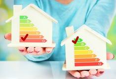 Begreppsjämförelse mellan det normala huset och det låga förbrukningshuset med energieffektivitetsvärdering Fotografering för Bildbyråer