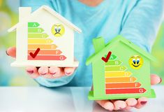 Begreppsjämförelse mellan det normala huset och det låga förbrukningshuset med energieffektivitetsvärdering Royaltyfria Bilder