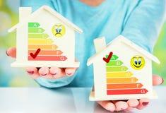 Begreppsjämförelse mellan det normala huset och det låga förbrukningshuset med energieffektivitetsvärdering Royaltyfri Fotografi