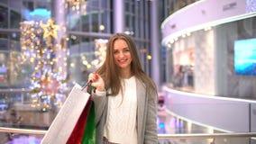 Begreppsjul som shoppar - härlig kvinna med mång--färgade packar i händer som går i köpcentrum på det nya året arkivfilmer