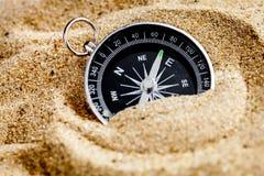 Begreppskompass i sand som söker betydelse av liv royaltyfria bilder