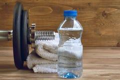 Begreppskonditionutrustning med hanteln, flaska av vatten och handduk Royaltyfri Bild