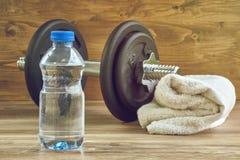 Begreppskonditionutrustning med hanteln, flaska av vatten och handduk Arkivfoto