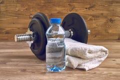 Begreppskonditionutrustning med hanteln, flaska av vatten och handduk Royaltyfria Bilder