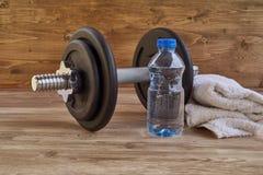 Begreppskonditionutrustning med hanteln, flaska av vatten och handduk Royaltyfri Foto