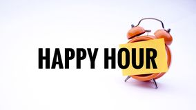Begreppsmässig bild av affärsidéen med lycklig timme för ord på en klocka med en vit bakgrund Selektivt fokusera Arkivbilder