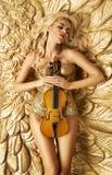 Begreppsmässig bild av den guld- kvinnan som rymmer en fiol Arkivbild