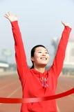Begreppsmässig bild av en asiatisk kvinna som segrar ett lopp Royaltyfri Fotografi