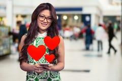 Begreppsmässig bild av kvinnan som smsar på mobiltelefonen med digitala frambragda röda hjärtor Arkivbild