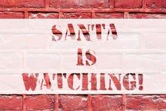 Begreppsmässig handhandstil som visar Santa Is Watching Affärsfototext att leverera gåvor som leksaker till allt som uppförs väl arkivfoto