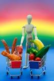 Begreppsmässig man, kött, grönsaker, på ljus regnbågebakgrund Arkivbilder