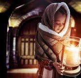 Begreppsmässig stående av en gullig liten flicka som rymmer en fackla arkivfoto