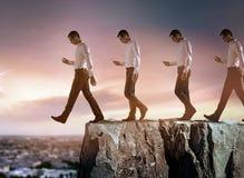 Begreppsmässig stående av en ung affärsman som ner faller från klippan royaltyfria foton